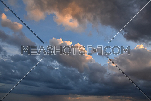 Beautiful dramatic early sunset cloudscape with fluffy ornge lit clouds over clear blue sky, low angle view