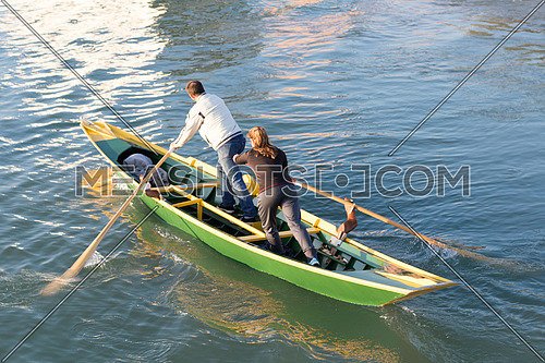 man and woman sailing a small boat in Venice canal