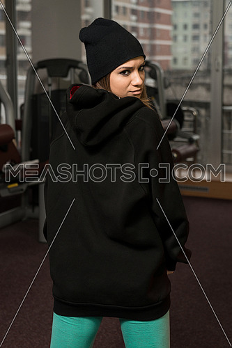 Young Sexy Woman In Black Hooded Sweatshirt Posing In Gym
