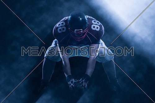 American football player starting football game on big modern american football field with lights and flares at night