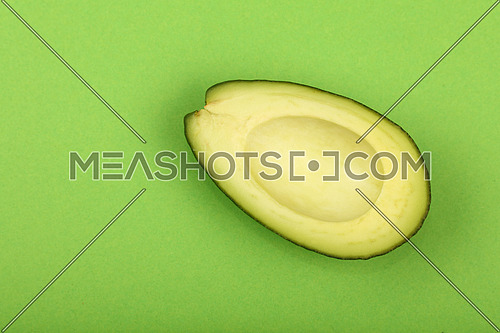 One fresh ripe avocado (Persea gratissima) half without pit stone on green paper background, detail, close up, elevated top view, elevated top view