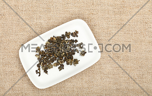 White small plate with dried green tea leaves on flax canvas tablecloth, close up, elevated top view, directly above