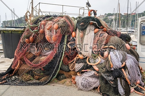 Fishing nets stacked on the waterfront after fishing day,quayside of the port of Varazze, Liguria Italy.