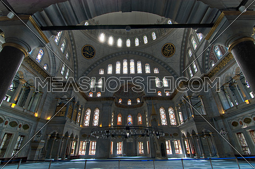 Interior of Nuruosmaniye Mosque, Istanbul, Turkey, with huge arches, decorated domes and colored stained glass windows