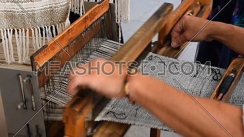 Close up man hands weave canvas with antique loom handweave machine, side view