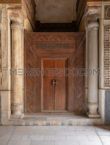 Old wooden door framed by wooden engraved panels decorated with geometric and floral patterns between two carved columns located at Sultan Qalawun Mausoleum, Cairo, Egypt