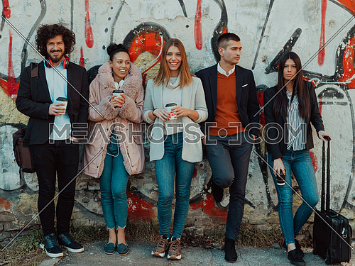 a group of diverse young businessmen on a break from work walk around the city, use smartphones, listen to music, and have fun