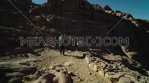 Follow shot for two male tourists exploring Sinai Mountain at day.