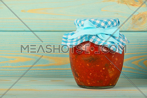 One glass jar of homemade pickled pepper, paprika and eggplant salad with checkered textile top decoration at blue painted vintage wooden surface