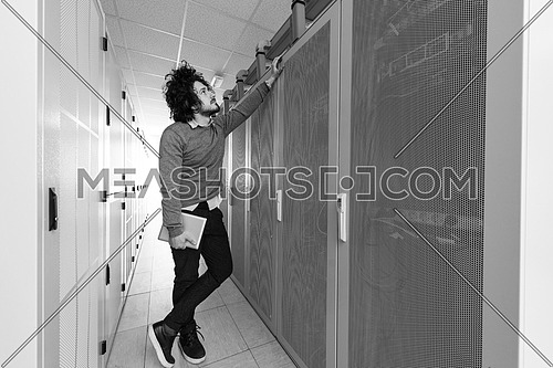 Male IT engineer working on a tablet computer in server room at modern data center