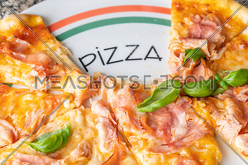 Fresh italian pizza with cheese(mozzarella), tomato, ham and small fresh basil leaves on the plate the inscription Pizza.
