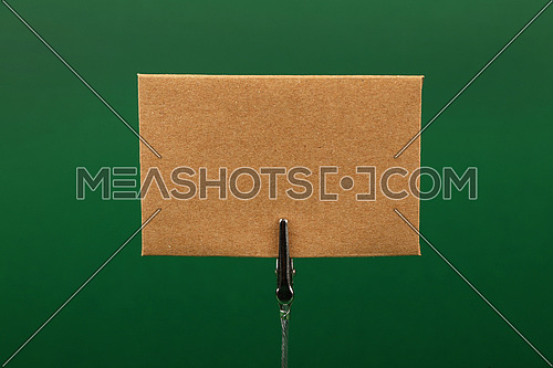 Blank brown kraft cardboard paper parchment sign with copy space on metal note holder over green background, front side view