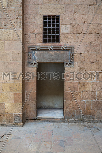 Ancient external old decorated bricks stone wall and opened door leading to Beit (house) Al Sehemy historical house, Cairo, Egypt