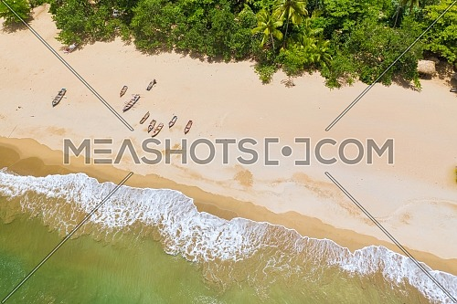 Aerial view of boats moored on the beach, Caribbean beach with waves.