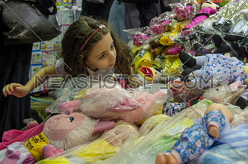 Little girl buying dolls from street seller at night.
