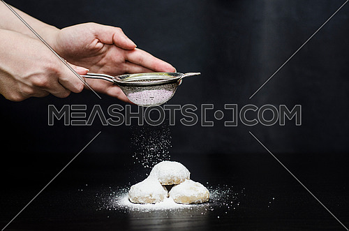 Kahk on a table and a woman holding a sprinkler of sugar and  sprinkling sugar on top of the kahk (cookies)  and flying sugar appears in the frame