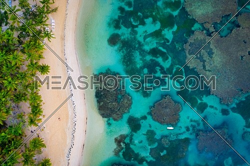 Drone shot of tropical beach with white boat anchored.Samana peninsula,Grand Bahia Principe El Portillo beach,Dominican Republic.
