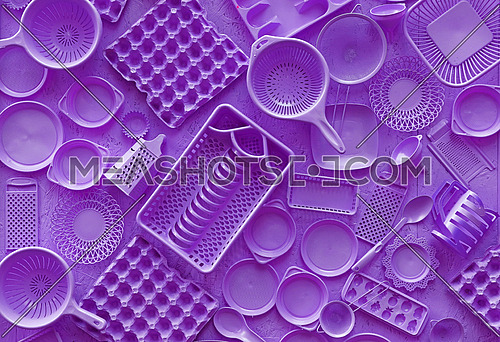 Close up flat lay of different purple violet color painted kitchen utensils and tools, grater, spoon, egg carton, plastic disposable plates, elevated top view, directly above