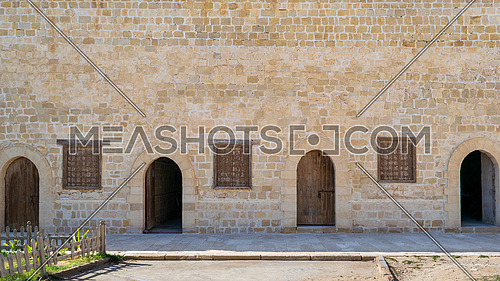 Four weathered wooden arched doors and three closed rusted wrought iron window on bricks stone wall and tiled stone floor