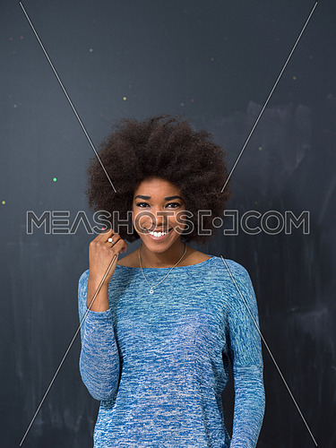 portrait of a beautiful friendly African American woman with a curly afro hairstyle and lovely smile isolated on a gray background