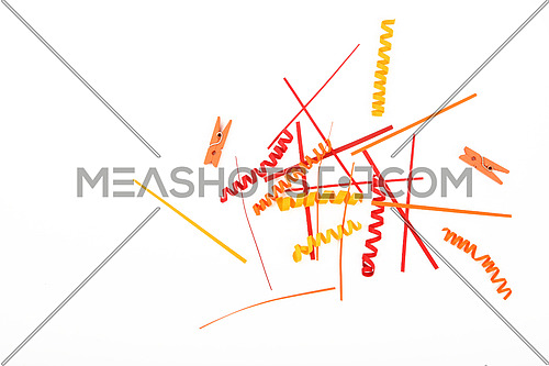 Small things matter, mixed colorful red and yellow paper pieces and wooden painted clothespins isolated on white background