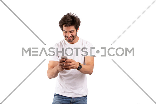 an Egyptian man holding a mobile phone dressed in white shirt and jeans