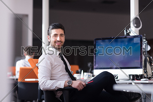 happy young business man  working on desktop computer at his desk in modern bright startup office interior