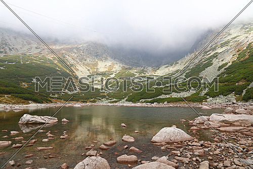 Beautiful tranquil landscape with Skalnate Pleso mountain lake, cloudy foggy day in High Tatra mountains