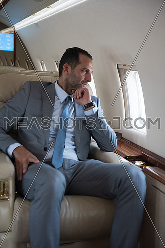 Portrait of a young middle eastern successful businessman sitting on a private jet with a tablet in hands
