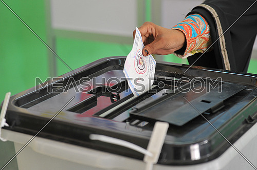The hand of an Egyptian lady puts the ballot paper on the ballot box on the last day of the presidential elections in Dahab city in South Sinai