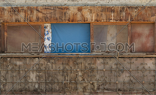 Exterior of old weathered shack with dirty windows and cloth curtains on sunny day in village