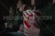 Close up for male hand holding and eating from popcorn container and young people in background at movie theatre.