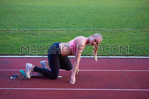 pixelated design of woman  sprinter leaving starting blocks on the athletic  track. Side view. exploding start