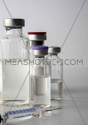 Several vials of glass next to syringe, conceptual image