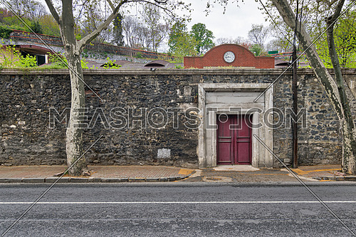 Closed old red wooden door, stone wall, and trees at Ciragan Street, Besiktas, Istanbul, Turkey