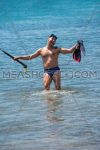 Young smiling fisherman with equipment standing in the shallow water of the sea while preparing for underwater fishing  active holiday concept