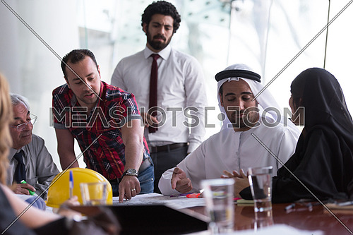 business people group on meeting, contractor and architect presenting plans and projects to middle eastern businessman investor