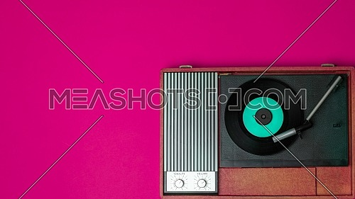 Old vinyl player and turnable on a fuchsia background. Entertainment 70s. Listen to music. Top view.