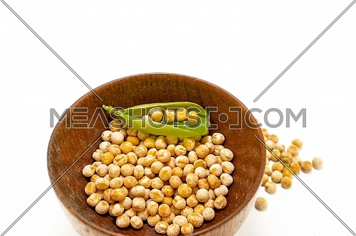 Dried peas in a rustic wooden bowl isolated on a white background