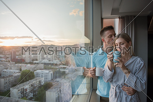 romantic happy young couple enjoying evening coffee and beautiful sunset landscape of the city while standing by the window