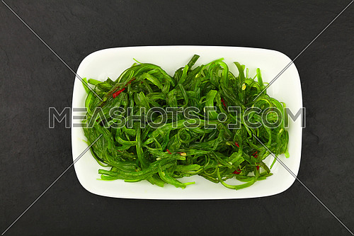Close up portion of green wakame seaweed salad on white plate over black slate board background, elevated top view, directly above
