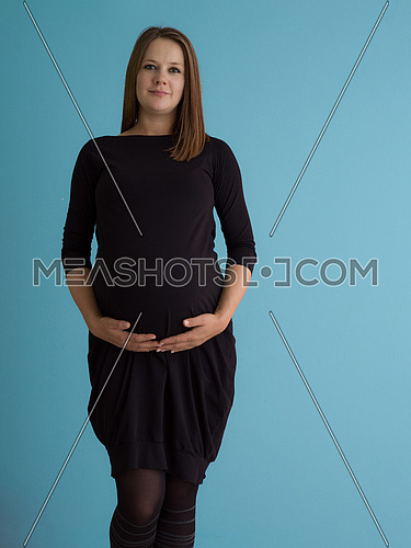 Portrait of happy pregnant woman with hands on belly isolated over blue background