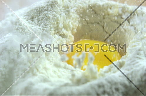 Close up Shot in Slow Motion for an egg falling in Flour