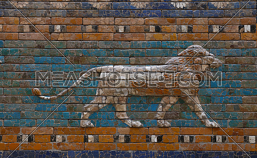 Close up beautiful glazed tiled bricks bas relief, decoration on ancient walls of Ishtar Gate of Babylon with images of Mesopotamian lions symbolizing the goddess, front view