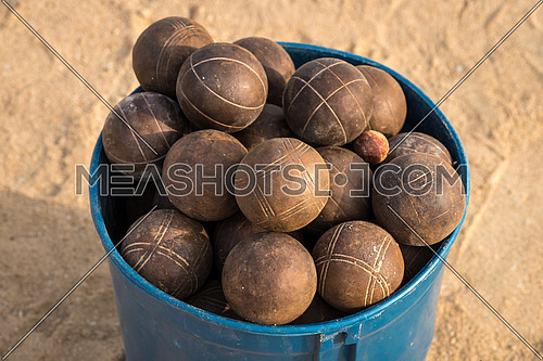In the picture a basket full of used balls to play ballgame( Bocce,Pentanque) on the beach.