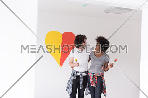Portrait of loving multiethnict couple with painted heart on wall