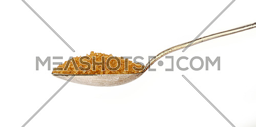 Close up one vintage silver metal spoon full of raw brown cane sugar isolated on white background, low angle side view