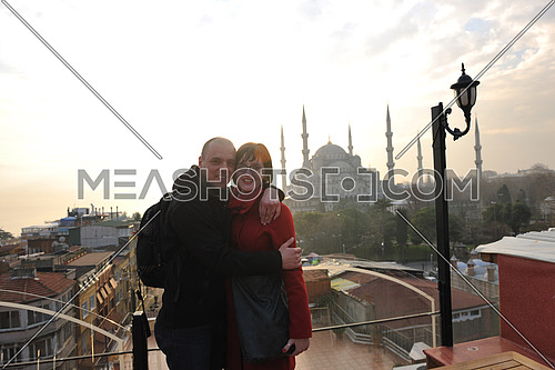 happy young couple portrait outdoor at sunny day in istanbul turkey with beautiful old mosque with sunset in background