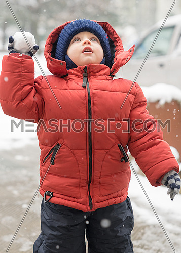 baby boy while it is snowing, looks upwards, holding a snowball in his hand, covered with a winter jacket and a woolen hat, close-up.