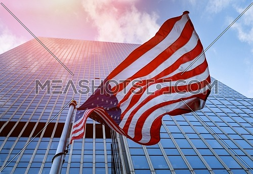 American flag waving against skyscrapers a blue sky.